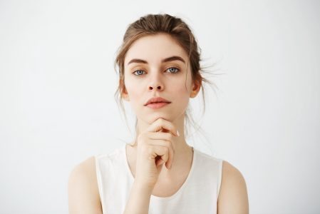 Portrait of young beautiful brunette girl looking at camera posing touching face over white background. Copy space.