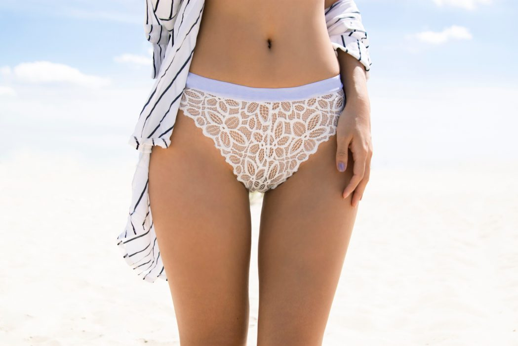 Slender legs and hips close up, female figure in the lower lace underwear.